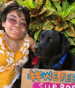 Maria and her care pup Shadow pose with a sign in support of farm workers.