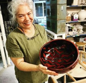 Gemma Yamamoto poses, showing off a bowl she made from clay.